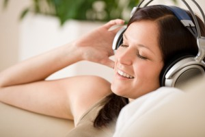 Smiling woman with headphones listen to music home